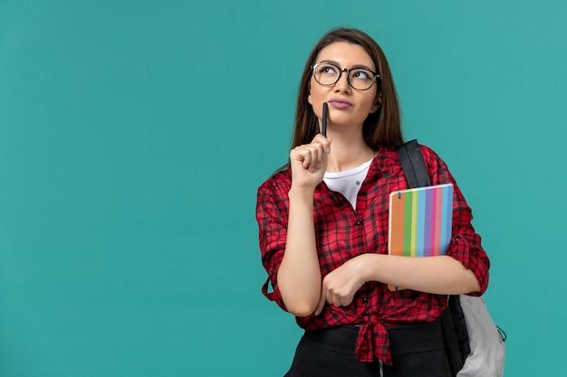 파란색 벽에 카피 북과 펜 생각을 들고 배낭을 착용하는 여성 학생의 전면보기