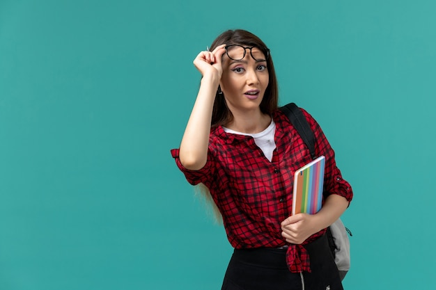 青い壁にコピーブックを保持しているバックパックを身に着けている女子学生の正面図