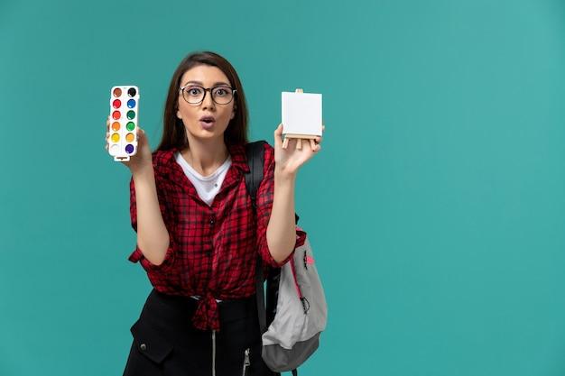 밝은 파란색 벽에 이젤과 페인트를 들고 배낭을 착용하는 여성 학생의 전면보기