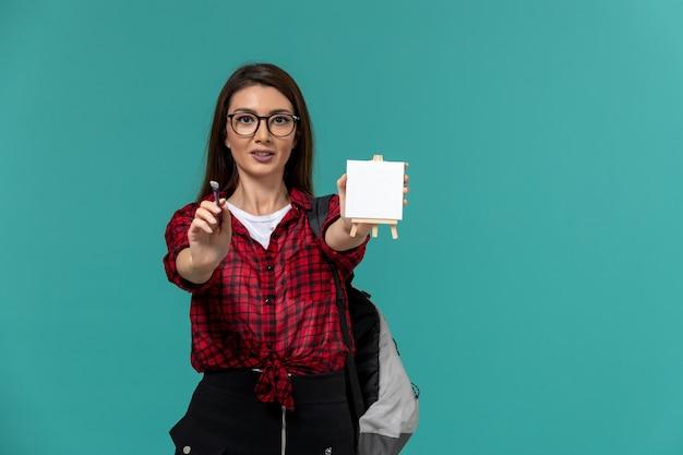 Вид спереди студентки в рюкзаке с мольбертом и кисточкой на голубой стене