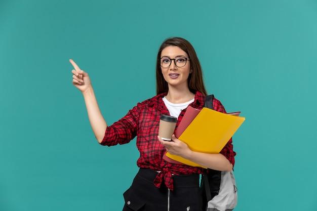 파란색 벽에 파일과 커피를 들고 배낭을 착용하는 여성 학생의 전면보기
