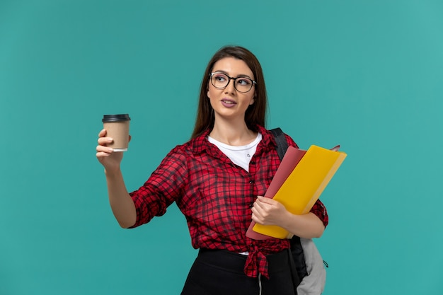Вид спереди студентки в рюкзаке с файлами и кофе на синей стене