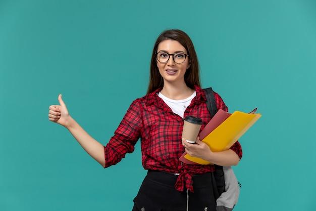 밝은 파란색 벽에 파일과 커피를 들고 배낭을 착용하는 여성 학생의 전면보기