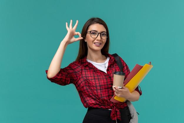 水色の壁にファイルとコーヒーを保持しているバックパックを身に着けている女子学生の正面図