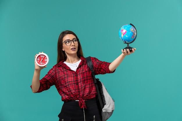 水色の壁に小さな地球儀と時計を保持しているバックパックを身に着けている女子学生の正面図