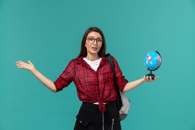 Вид спереди студентки в рюкзаке с маленьким глобусом на голубой стене