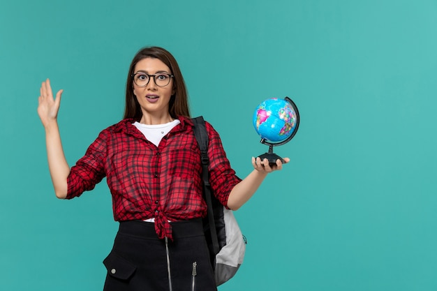 水色の壁に小さな地球儀を保持しているバックパックを身に着けている女子学生の正面図