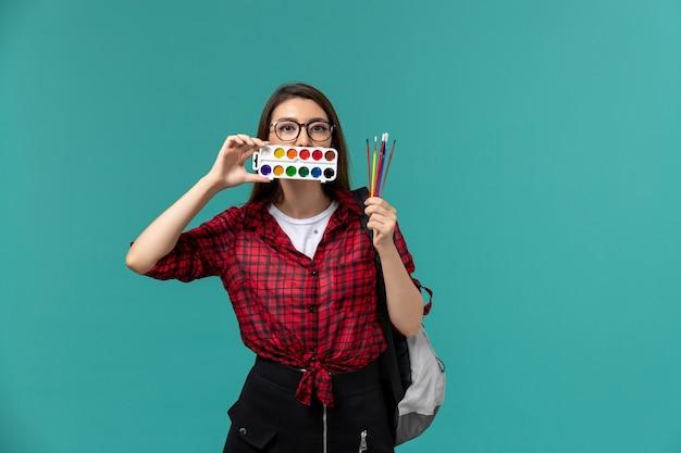파란색 벽에 페인트와 술을 들고 배낭을 착용하는 여성 학생의 전면보기