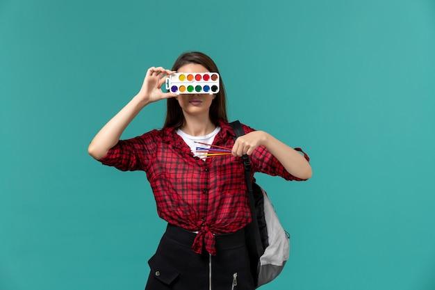 Вид спереди студентки в рюкзаке с красками и кисточками на синей стене