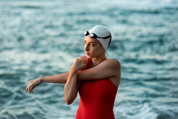 Женщина-пловец, растягиваясь перед плаванием, вид спереди