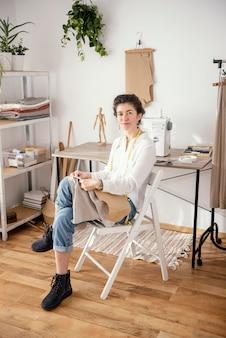 スタジオで働く女性の仕立て屋の正面図