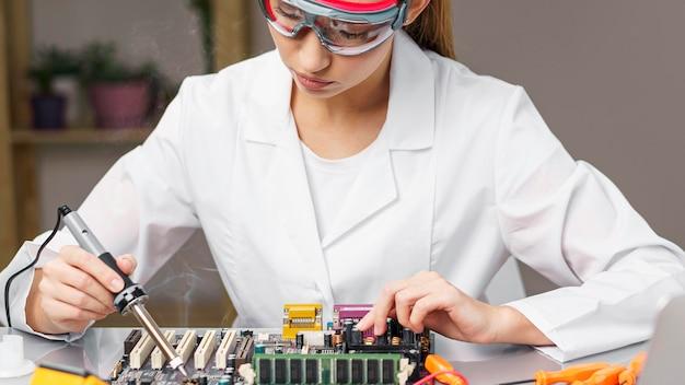 납땜 인두 및 전자 보드가있는 여성 기술자의 전면보기