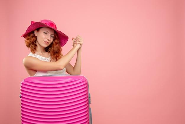분홍색 벽에 분홍색 가방 여성 관광객의 전면보기