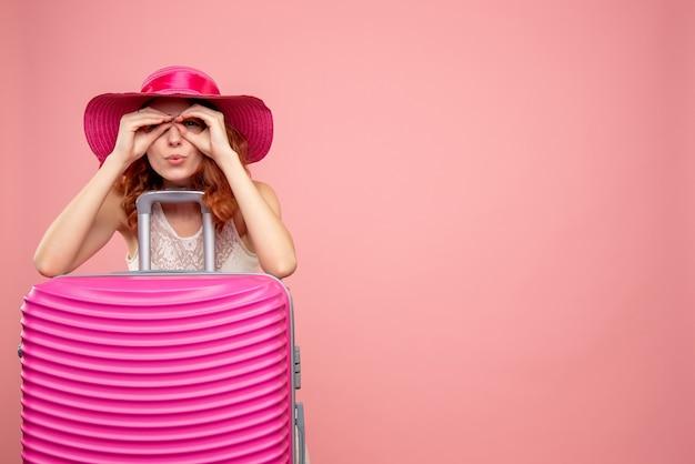 분홍색 벽에 분홍색 가방 여성 관광객의 전면보기 무료 사진