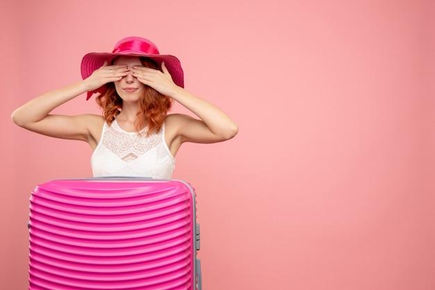 ピンクの壁にピンクのバッグを持つ女性観光客の正面図