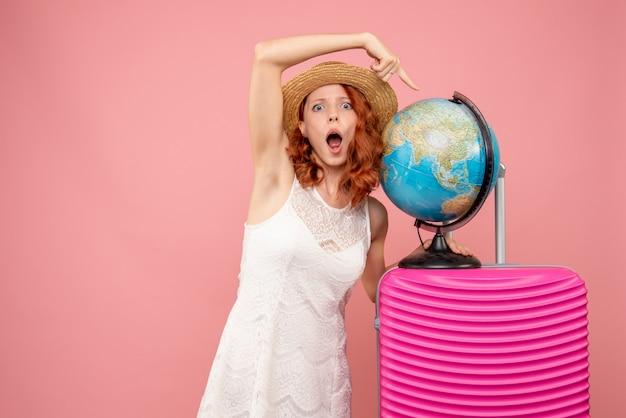 Вид спереди туристки с розовой сумкой на розовой стене