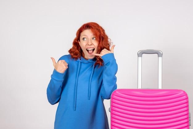 白い壁にピンクのバッグと女性観光客の正面図
