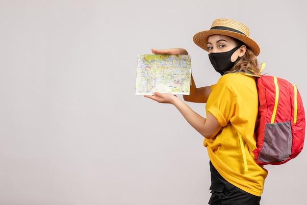 白い壁に地図を保持している黄色のtシャツの女性旅行者の正面図