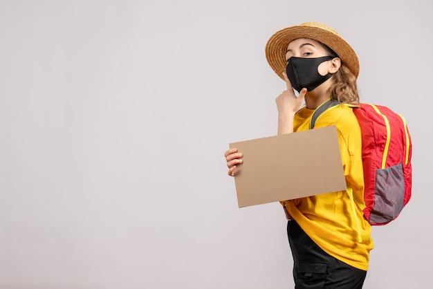 灰色の壁に彼女のあごに手を置いて段ボールを保持しているバックパックを持つ女性旅行者の正面図