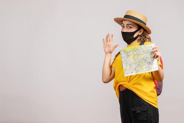 白い孤立した壁に地図を保持しているバックパックと女性旅行者の正面図