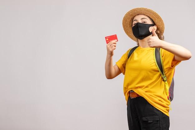 灰色の壁に親指をあきらめてカードを保持しているバックパックと女性旅行者の正面図
