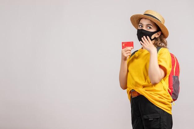 灰色の壁にカードを保持しているバックパックと女性旅行者の正面図