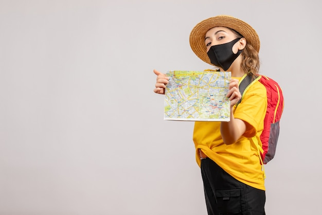 白い壁に地図を保持しているバックパックと女性旅行者の正面図