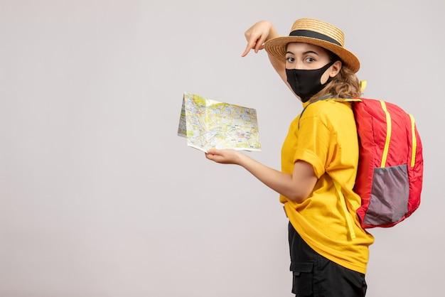 白い壁の上の地図を指している黒いマスクを持つ女性旅行者の正面図