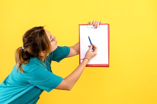 Вид спереди ветеринара-женщины, держащего анализы на желтой стене