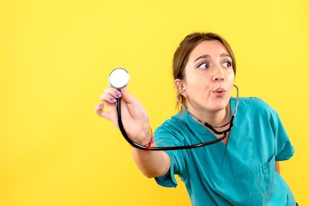 노란색 벽에 청진기를 사용하여 여성 수의사의 전면보기
