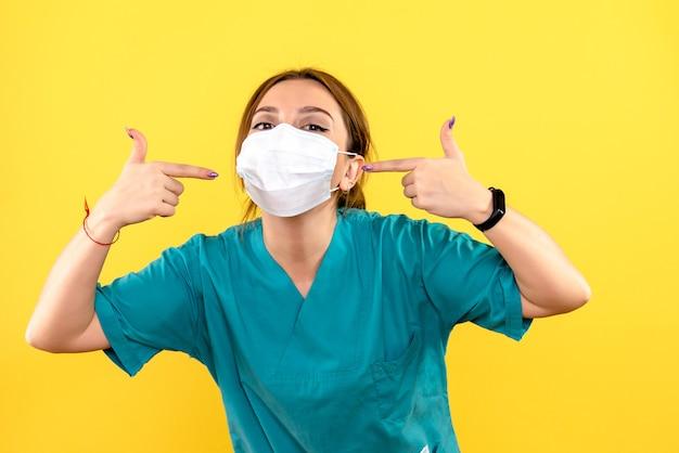 노란색 벽에 마스크를 쓰고 여성 수의사의 전면보기
