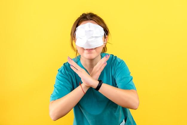 노란색 벽에 얼굴에 마스크를 쓰고 여성 수의사의 전면보기