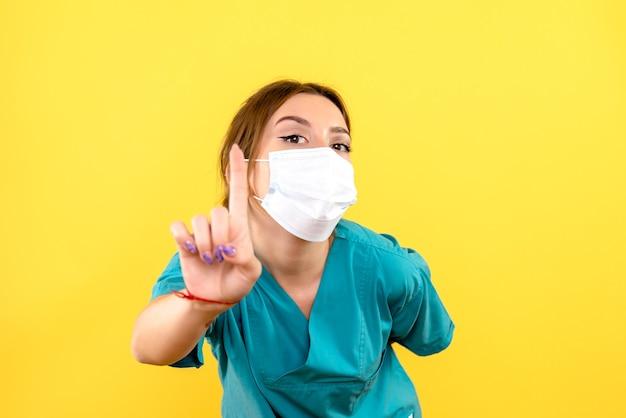 黄色い床のパンデミック健康covid-にマスクを身に着けている女性獣医の正面図