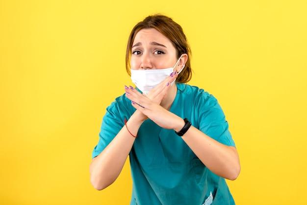 黄色の壁にマスクを身に着けている女性獣医の正面図