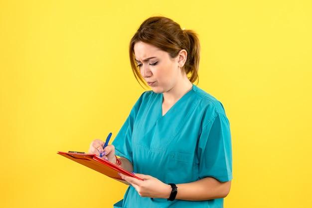 노란색 벽에 메모를 작성하는 여성 수의사의 전면보기