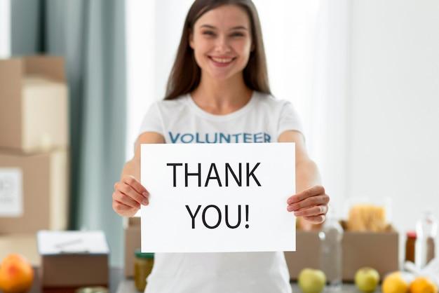 Женщина-волонтер благодарит вас за помощь с пожертвованиями продуктов питания, вид спереди