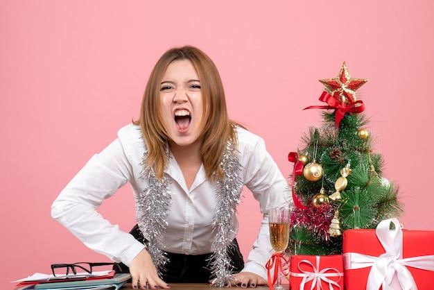 크리스마스 주위 여성 노동자의 전면보기 핑크에 선물