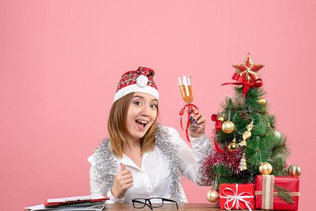 핑크에 샴페인 잔으로 크리스마스를 축하하는 여성 노동자의 전면보기