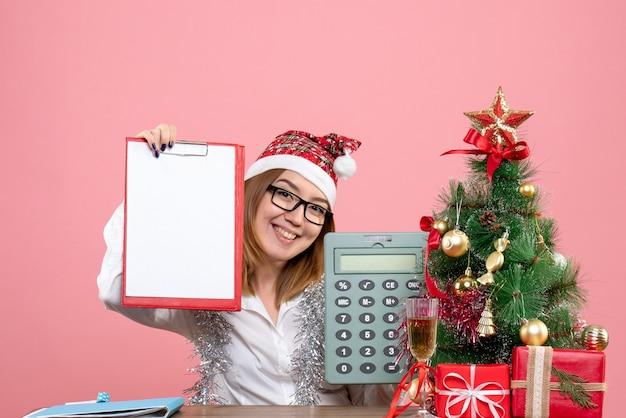 핑크에 계산기와 파일 메모를 들고 여성 노동자의 전면보기