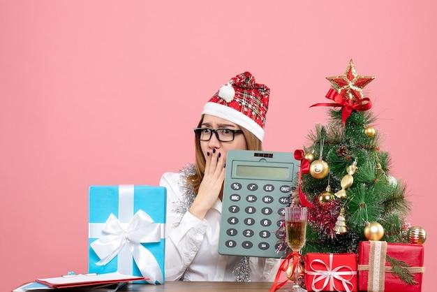 Вид спереди работницы, держащей калькулятор вокруг подарков на розовом