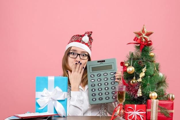ピンクのプレゼントの周りに電卓を持っている女性労働者の正面図