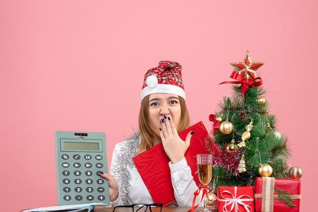 ピンクの電卓を保持している女性労働者の正面図
