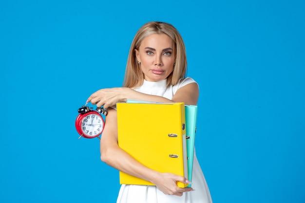青い壁にフォルダーと時計を保持している女性労働者の正面図