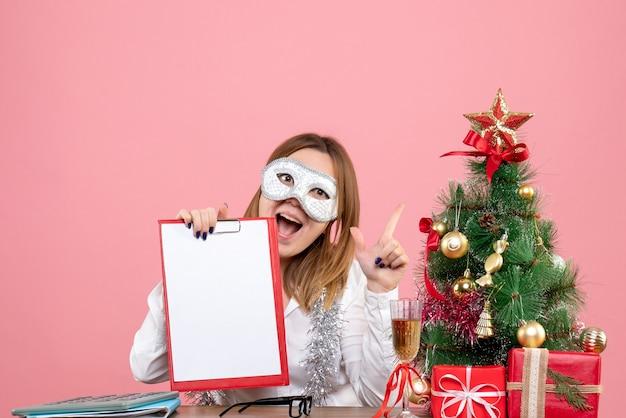 ピンクのファイルノートとパーティーマスクの女性労働者の正面図