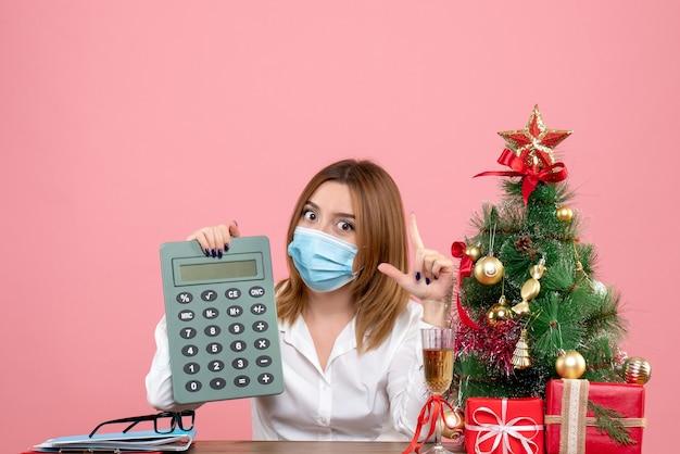 ピンクの電卓を保持している滅菌マスクの女性労働者の正面図