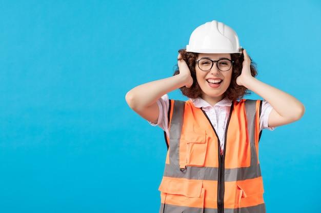 Вид спереди работницы в униформе на синей стене