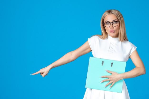 青い壁に青いフォルダーを保持している白いドレスの女性労働者の正面図