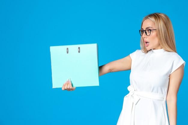 파란 벽에 파란 폴더를 들고 있는 흰 드레스를 입은 여성 노동자의 전면 모습