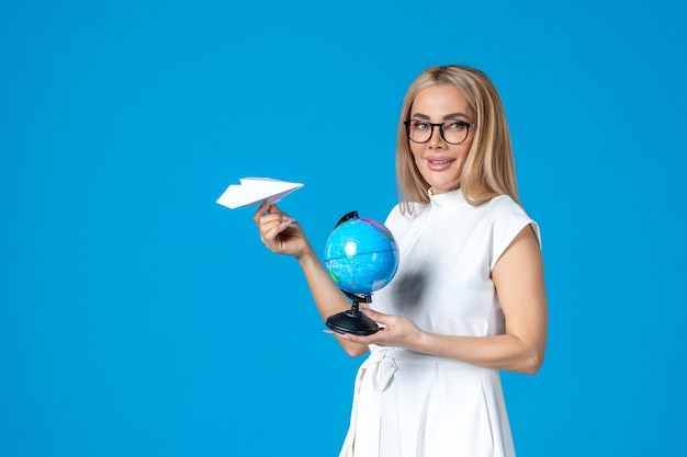 青い壁に地球儀と紙飛行機を保持している白いドレスの女性労働者の正面図