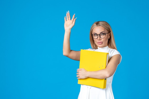 フォルダーを保持し、青い壁に誰かに挨拶する白いドレスの女性労働者の正面図